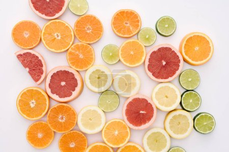 top view of various citrus fruits slices spilled on white surface