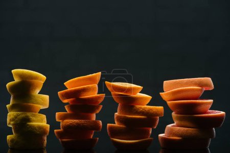 stacked slices of various ripe citrus fruits slices isolated on black