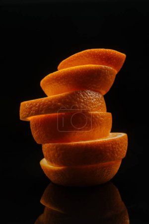 close-up shot of stacked slices of ripe orange isolated on black