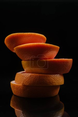 close-up shot of stacked slices of grapefruit isolated on black