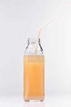 glass bottle of fresh apple juice on white