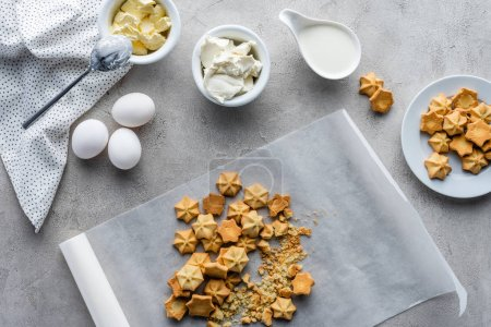 flat lay with cookies, raw chicken eggs, butter and sour cream for making pie arranged on grey tabletop