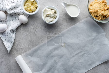 flat lay with baking paper, crushed cookies, raw chicken eggs and butter for making pie on grey surface