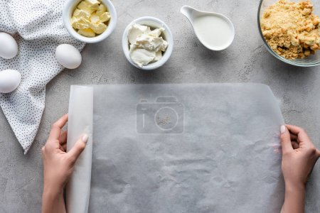 cropped shot of woman holding baking paper with arranged ingredients for pie on grey tabletop