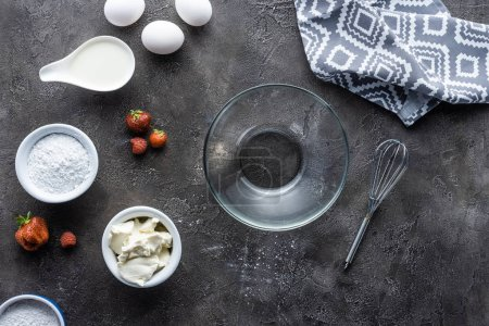 flat lay with arrangement of ingredients for homemade pie and empty bowl on dark grey surface