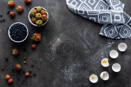 Photo for Flat lay with fresh berries, eggshells and linen in dark grey surface - Royalty Free Image