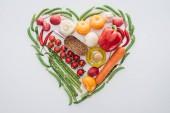 """Постер, картина, фотообои """"вид сверху сердца, сделанные из зеленого горошка, спаржа и спелые овощи со специями, изолированные на белом"""""""