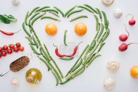 Photo for Top view of heart made of fresh green peas and asparagus and smiley face from tomatoes and chili peppers isolated on white - Royalty Free Image