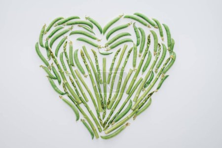 top view of heart made of fresh green peas and asparagus isolated on white