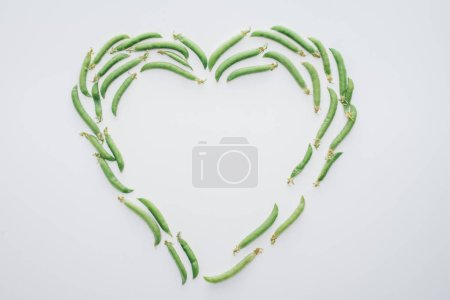 top view of heart made of fresh green peas isolated on white