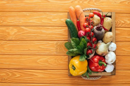 top view of fresh raw healthy vegetables in box on wooden table top