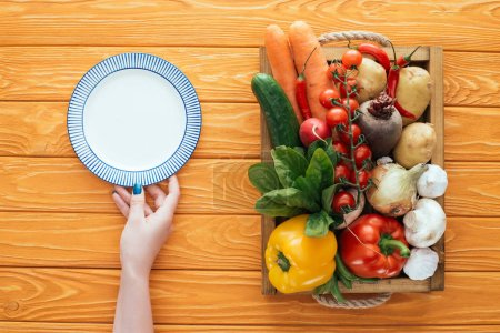 cropped shot of person holding empty round plate and fresh raw vegetables in box on wooden table top