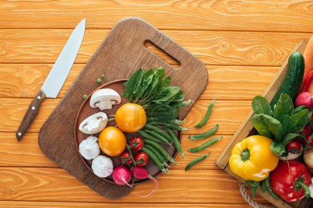 top view of fresh raw vegetables in box and in plate on wooden cutting board