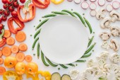 top view of empty round white plate and organic vegetables isolated on white