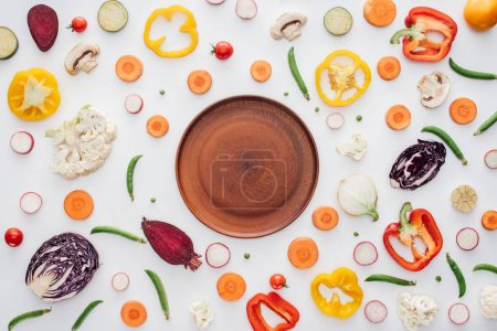 top view of empty round plate and fresh sliced organic vegetables isolated on white