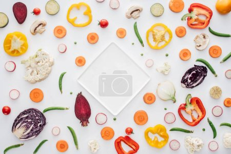 top view of empty white plate and fresh sliced vegetables isolated on white