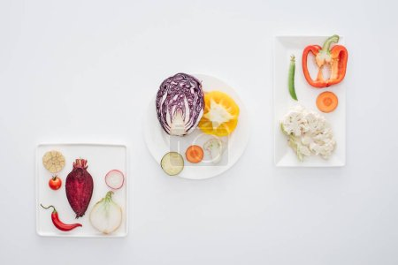 top view of fresh raw healthy vegetables on white plates isolated on white