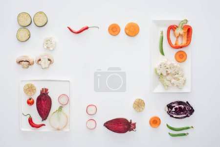 top view of square white plates and fresh sliced vegetables isolated on white