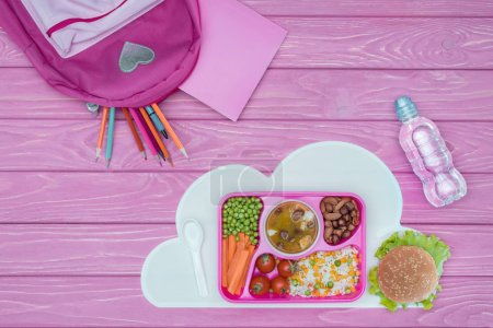 top view of tray with kids lunch for school, pink bag and pencils on pink table