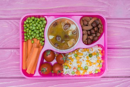 top view of tray with kids lunch for school on pink table