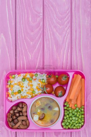top view of tray with kids lunch for school on violet wooden table