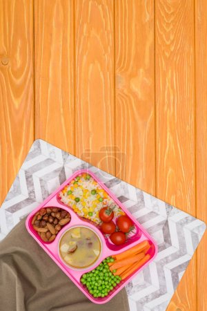 top view of tray with kids lunch for school with napkins on orange wooden table