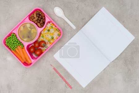 top view of tray with kids lunch for school and open notebook on marble table