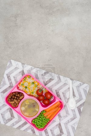top view of tray with kids lunch for school on napkin on marble table