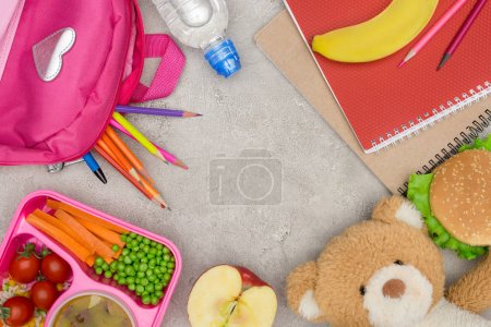 top view of tray with kids lunch for school, bag with pencils and notebooks on marble table