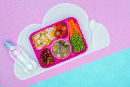 top view of tray with kids lunch for school and bottle of water on violet and blue table