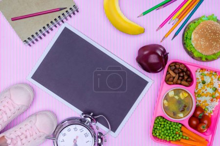 top view of blackboard and tray with kids lunch for school on trendy violet surface