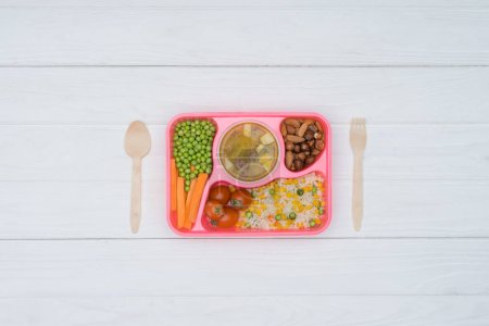 top view of tray with kids lunch for school and wooden spoon and fork on table