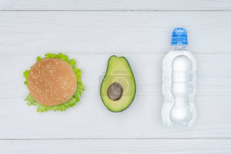 top view of burger, avocado and plastic bottle of water on wooden table