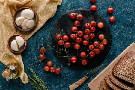 Ingredients for sandwiches with tomatoes and mozzarella on dark blue table