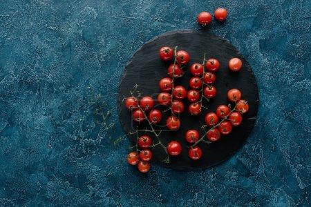 Red ripe cherry tomatoes on dark slate board