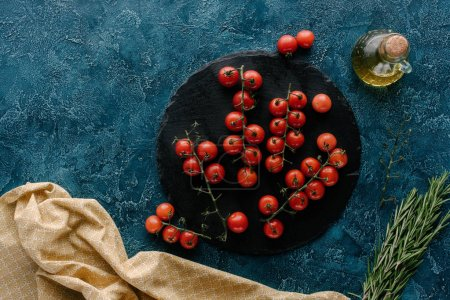 Dark slate board with cherry tomatoes and oil bottle on blue table