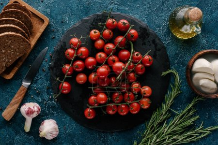 Dark slate board with red tomatoes on blue table with bread and condiments