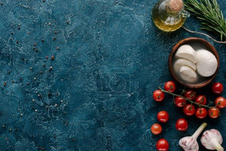 Mozzarella cheese with tomatoes and condiments on dark blue table