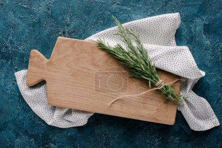 Photo for Wooden cutting board with rosemary herb on dark blue table - Royalty Free Image