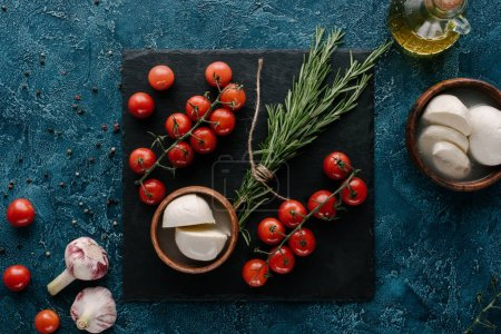 Mozzarella and red tomatoes on dark slate board with rosemary