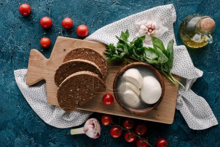 Wooden board with mozzarella and bread on dark blue table with red tomatoes