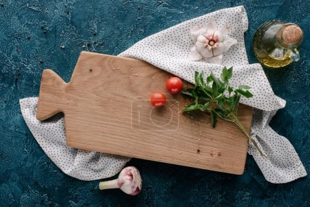 Cutting board with tomatoes and basil on dark blue table