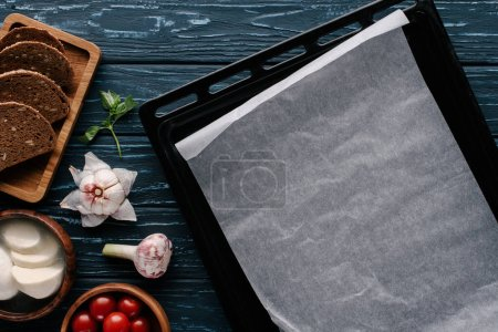 Empty baking sheet on dark wooden table by cooking ingredients and tomatoes
