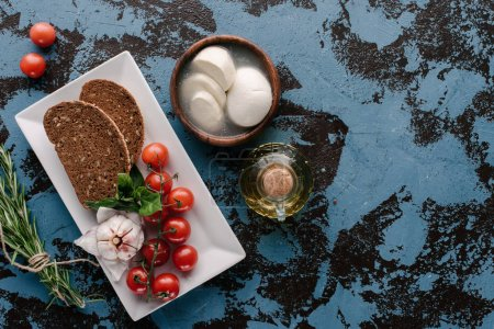 Plate with tomatoes an bread on dark blue table with mozzarella and oil