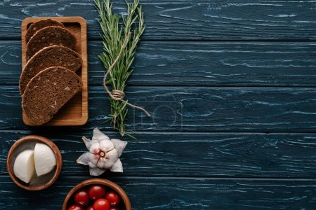 Photo for Mozzarella cheese and tomatoes on dark wooden table with rosemary and garlic - Royalty Free Image