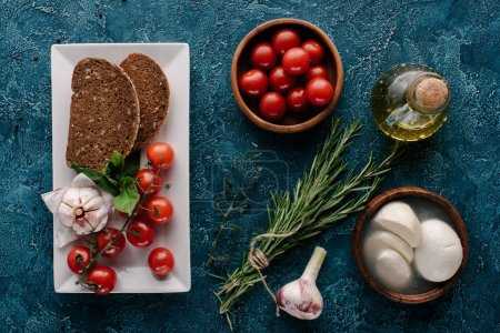 Mozzarella cheese and tomatoes on dark blue table with bread and herbs