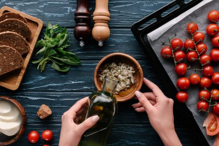 Photo for Cropped view of female hands adding oil to garlic on dark wooden table with tomatoes and herbs - Royalty Free Image