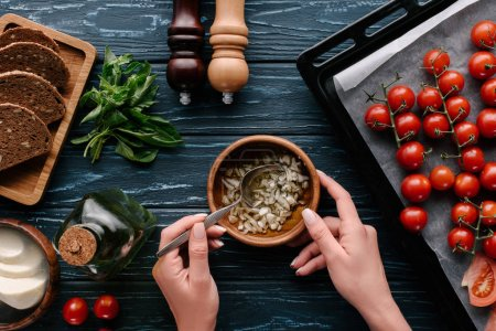 Cropped view of female hands cooking garlic oil on dark wooden table with tomatoes and herbs