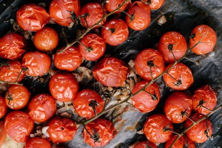 Baked cherry tomatoes with oil and garlic on pan