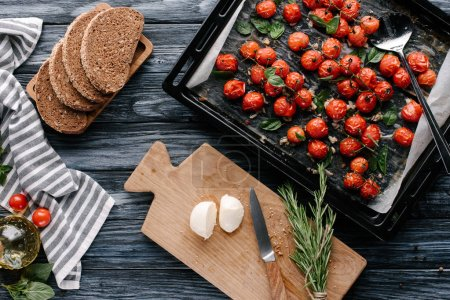 Pan with baked tomatoes and pieces of cheese and bread on dark wooden table